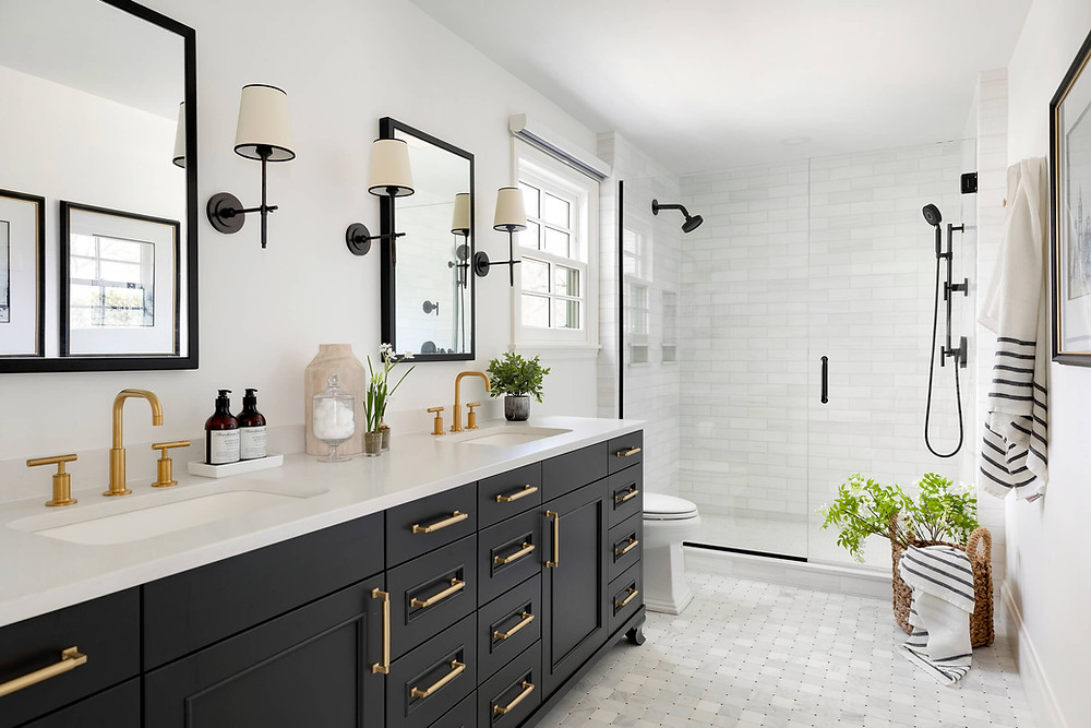 Black bathroom vanity with gold hardware and floor to ceiling marble tile.