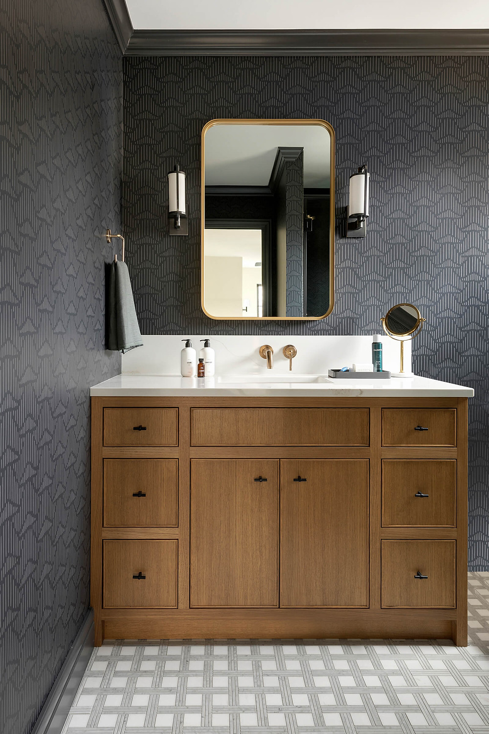 Moody bathroom design, patterned wallpaper, stone mosaic floor tile, white oak vanity with gold and black fixtures.