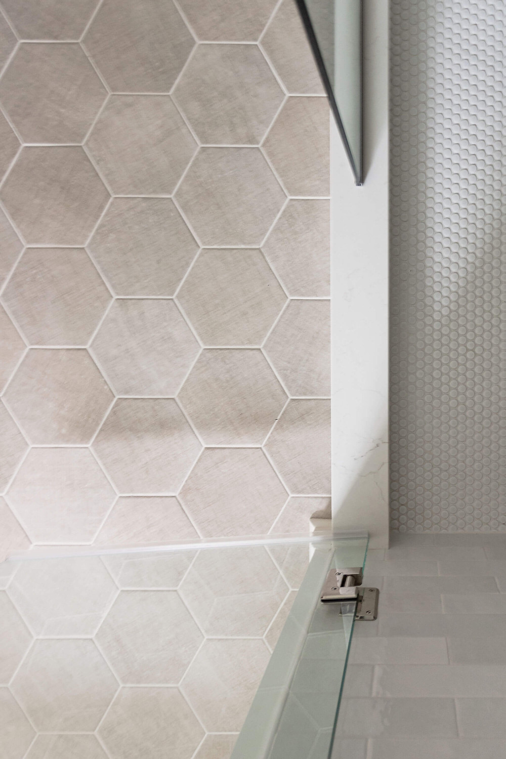 Primary owners suite tile selections on the shower and main floor including an ivory hexagon and matte white penny round tile
