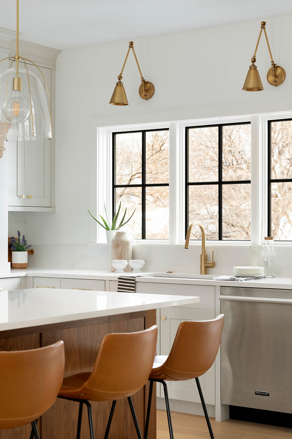 Black windows, painted light cabinetry with gold fixtures.