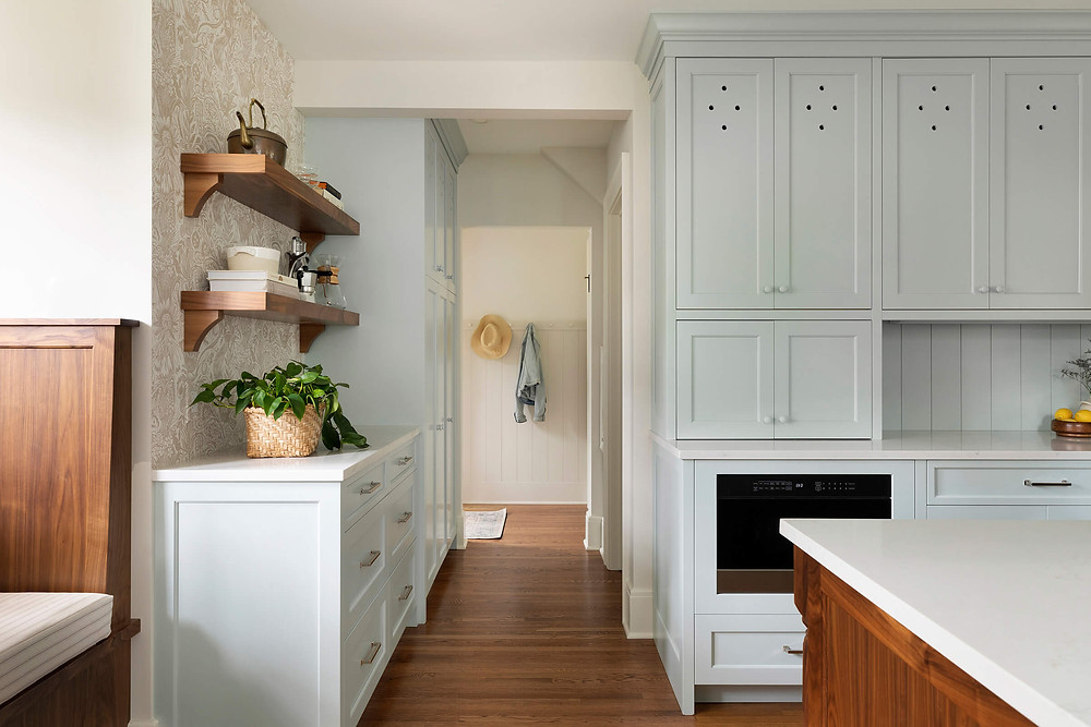 Modern charming English Colonial inspired kitchen with apron front sink filled with wildflowers, charming custom blue cabinetry and walnut built in dining booth