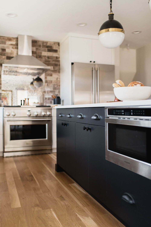 Microwave drawer in black kitchen island, red oak hardwood flooring, exposed range hood and brick backsplash