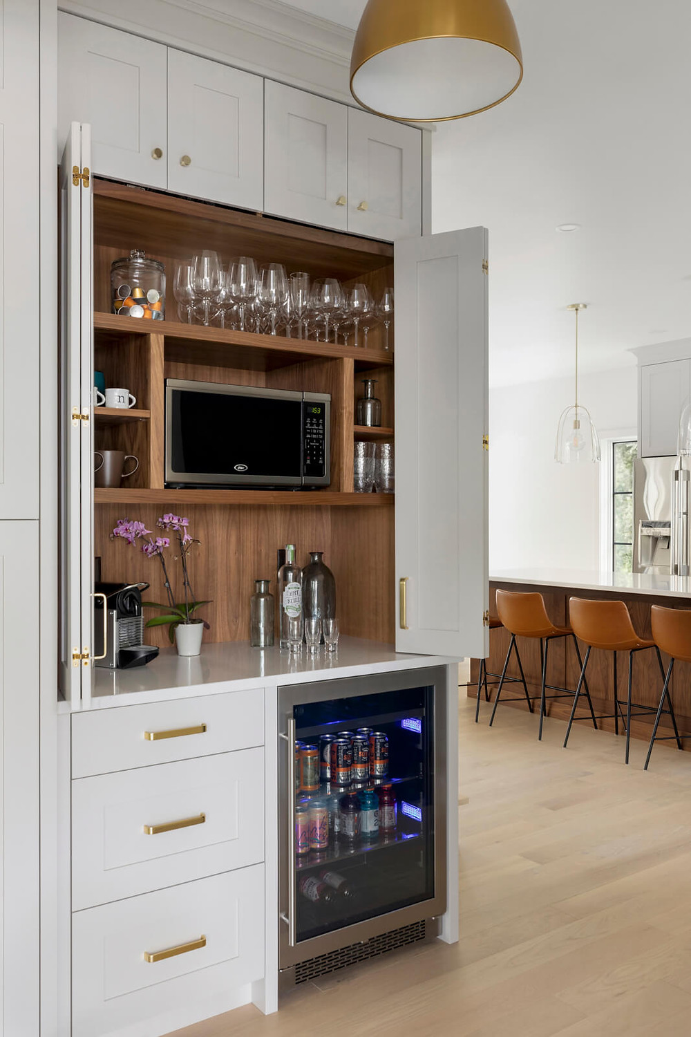 Custom walnut paneled kitchen pantry with retractable bifold doors to conceal microwave and bar.