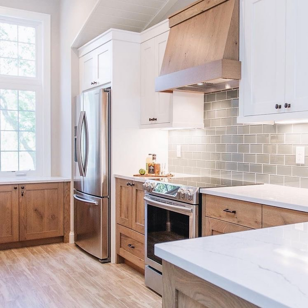 White and white oak kitchen cabinets with green glass subway backsplash tile and custom wood range hood