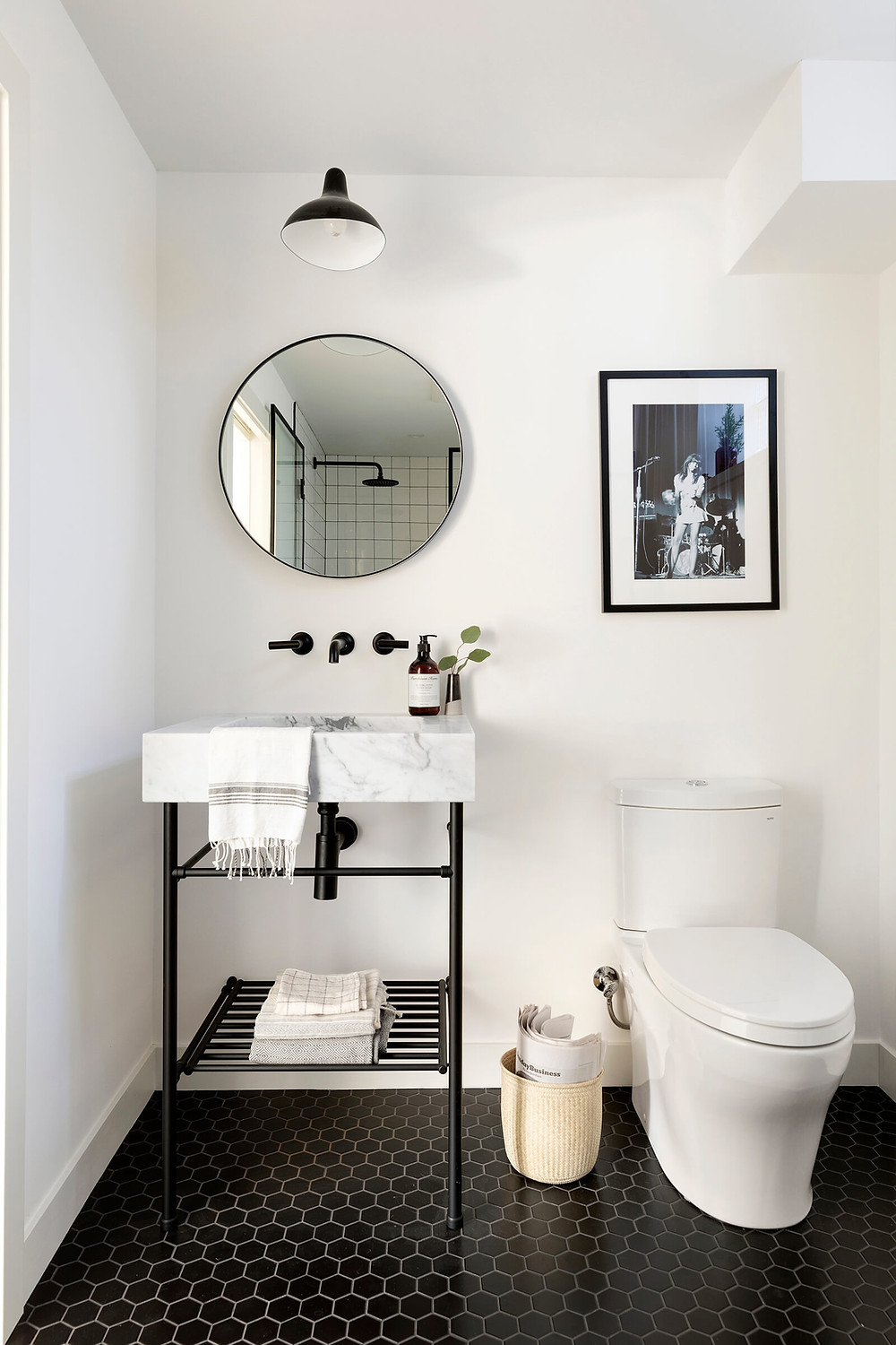 Custom marble console vanity in black and white bathroom with black hexagon floor tile, wall mount faucet and plumbing fixtures