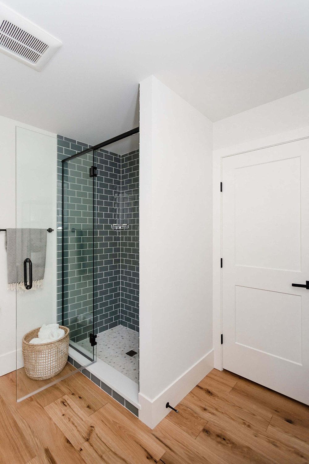 Contemporary guest bathroom with dark maple vanity, blue glass field tile and marble hexagon shower floor