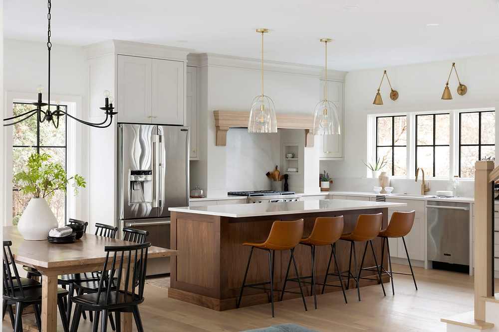 Open concept kitchen with walnut island, brass light fixtures, casual dining table with farmhouse black chandelier
