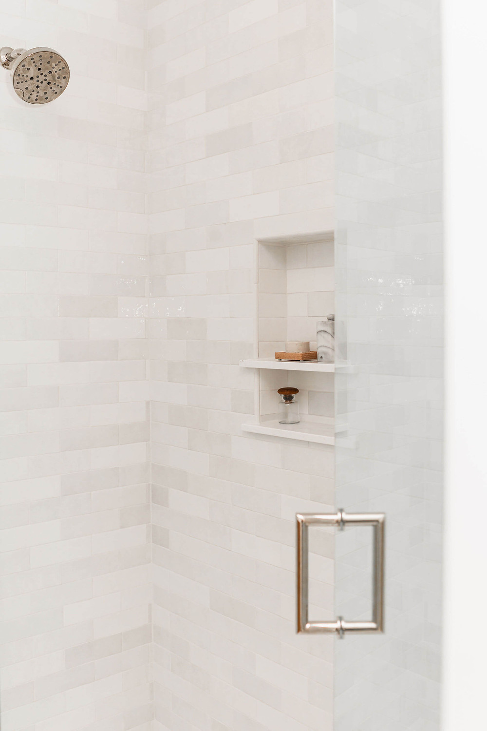 Primary owners suite walk in shower with white artisan subway wall tile and matte white penny round shower pan tile, polished nickel finishes