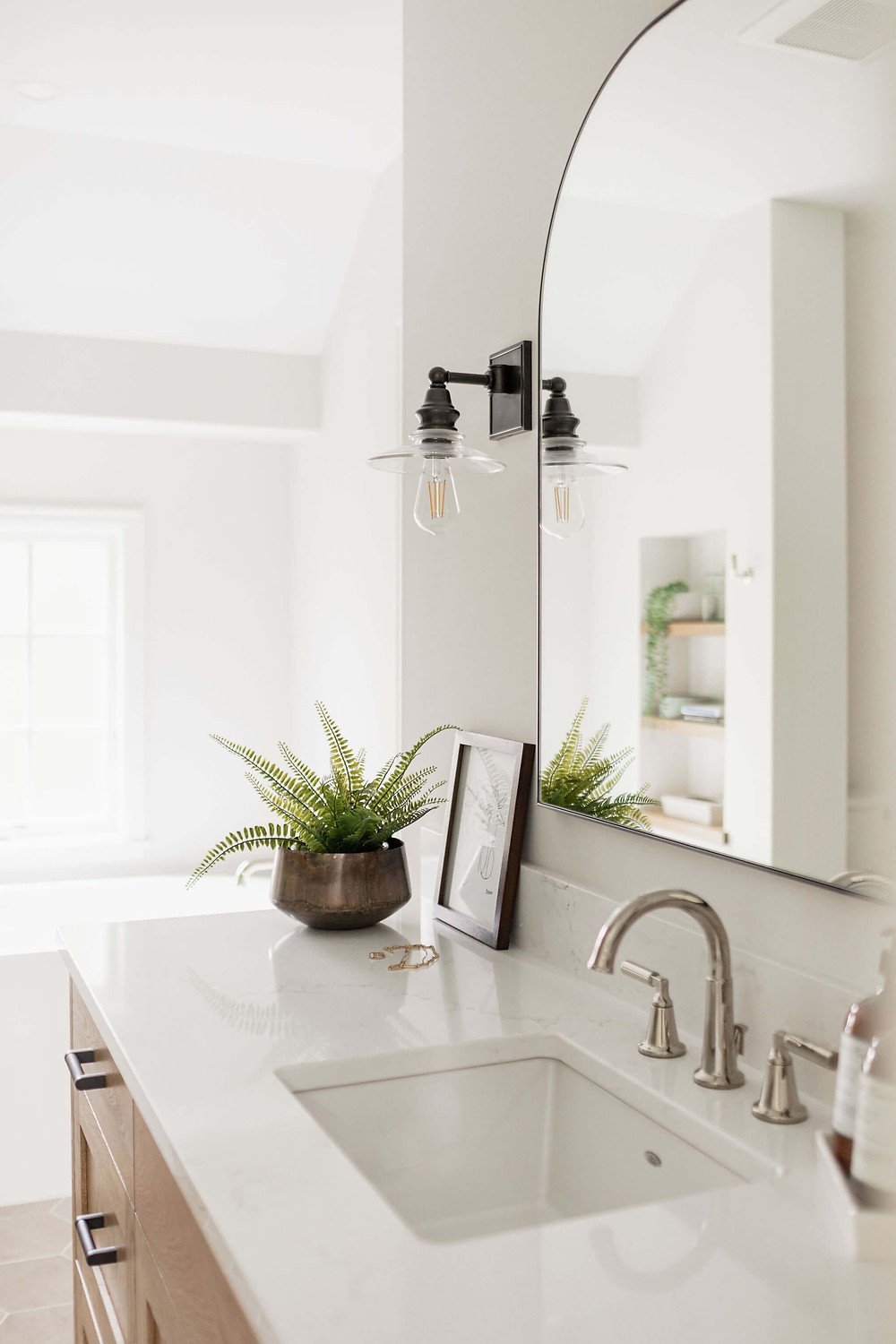 Primary owners suite bathroom custom vanity with white quartz countertop, polished nickel sink faucet and black industrial inspired wall sconces
