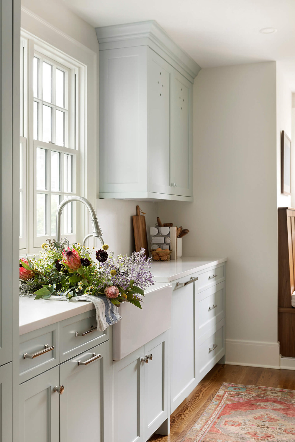 Modern charming English Colonial inspired kitchen with apron front sink filled with wildflowers, charming custom blue cabinetry and polished nickel hardware