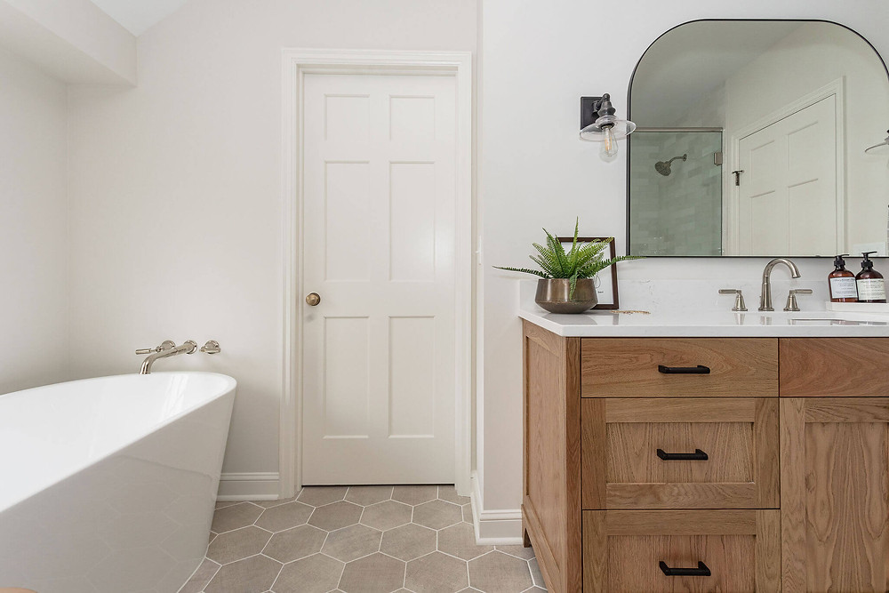 Primary owners suite bathroom with ivory hexagon floor tile, wall mount polished nickel tub filler with freestanding bathtub, custom stain white oak vanity with black hardware and accents