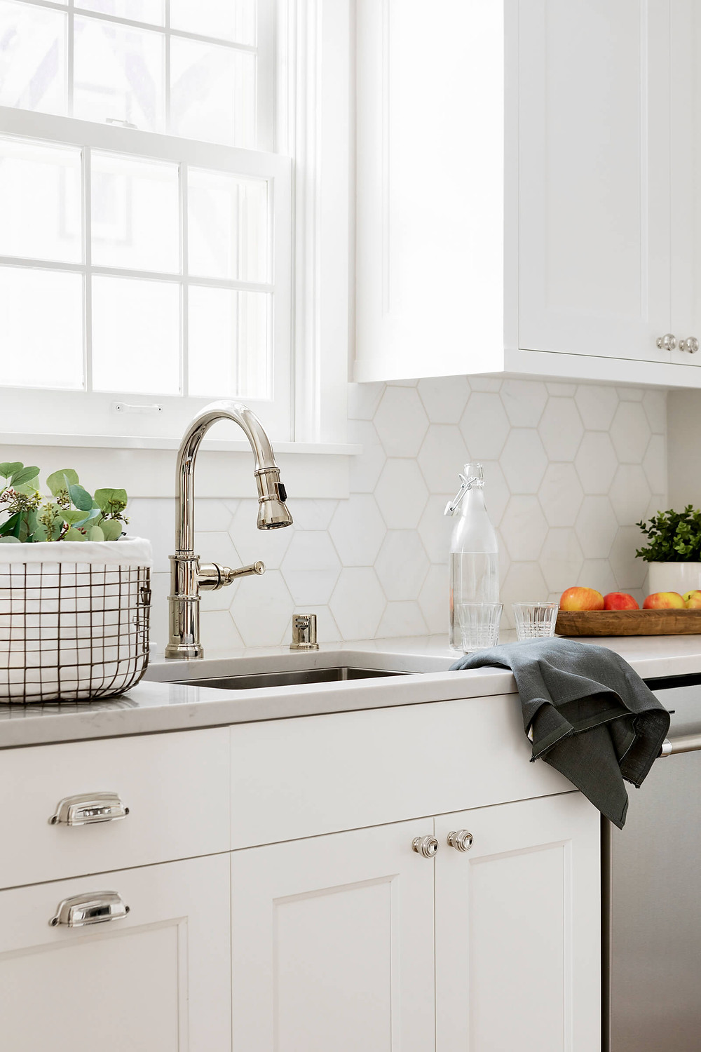 Kitchen remodel with white cabinetry, marble hexagon backsplash tiles, polished nickel finishes while sharing ways to live a sustainable lifestyle.