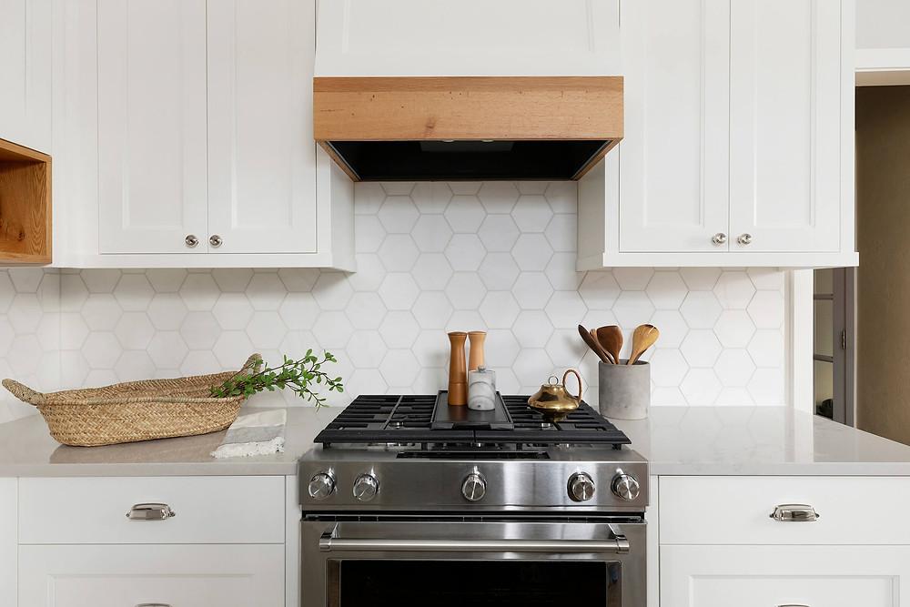 Kitchen range, with reclaimed oak hood and hexagon marble backsplash
