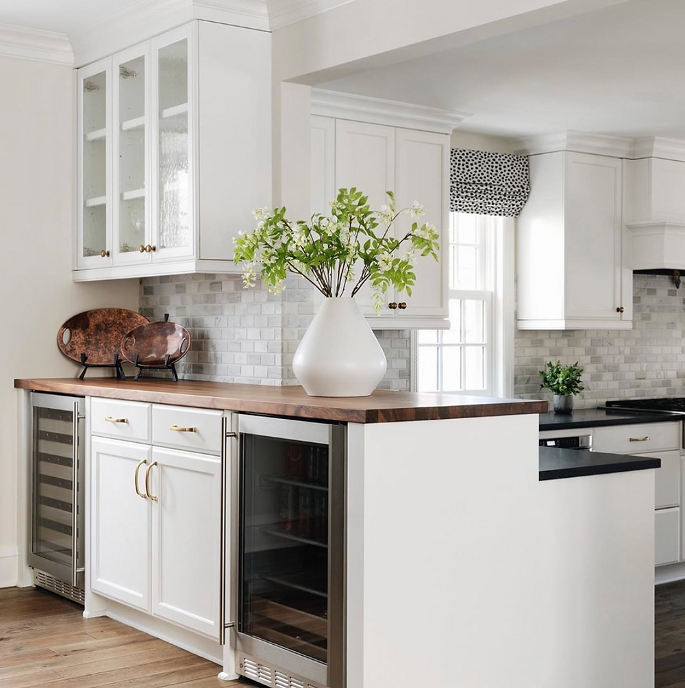 Contemporary white kitchen with butcher block countertop over bar with wine fridge and marble backsplash tile