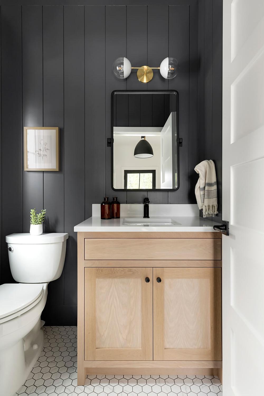 moody powder bathroom with custom white oak vanity, hexagon tile, black shiplap paneling