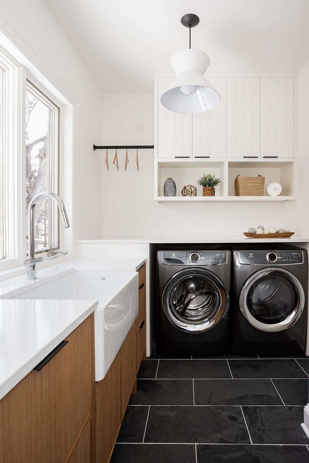 Scandinavian designed laundry room mudroom with rift white oak cabinetry, large apron sink, slate tile floor and white quartz countertop