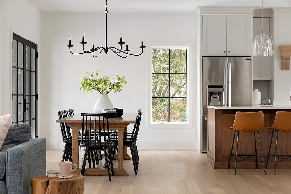 Spacious open concept modern farmhouse kitchen and dining room with wide plank engineered white oak flooring, black windows and modern furniture