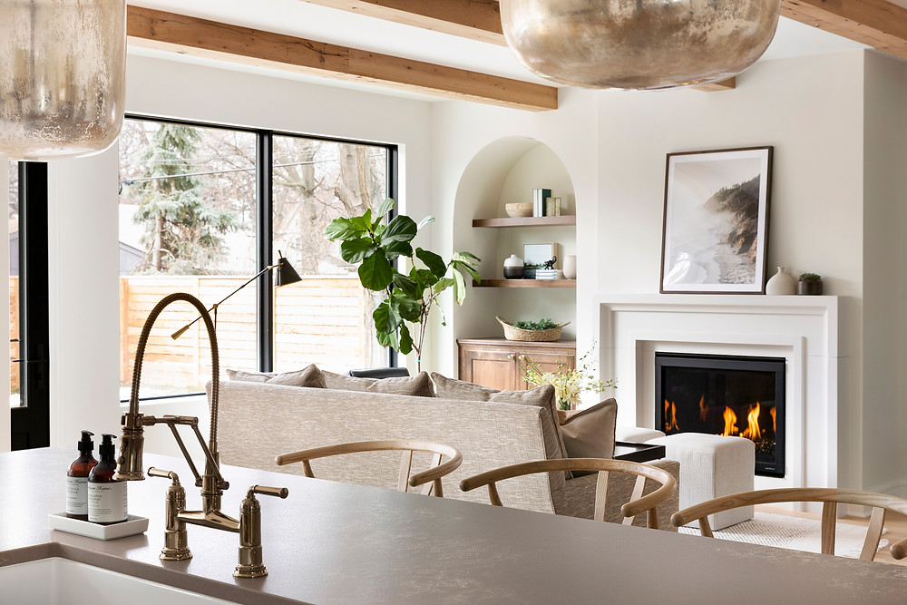 Modern Tudor living room design, arched bookcase, reclaimed wood beams.