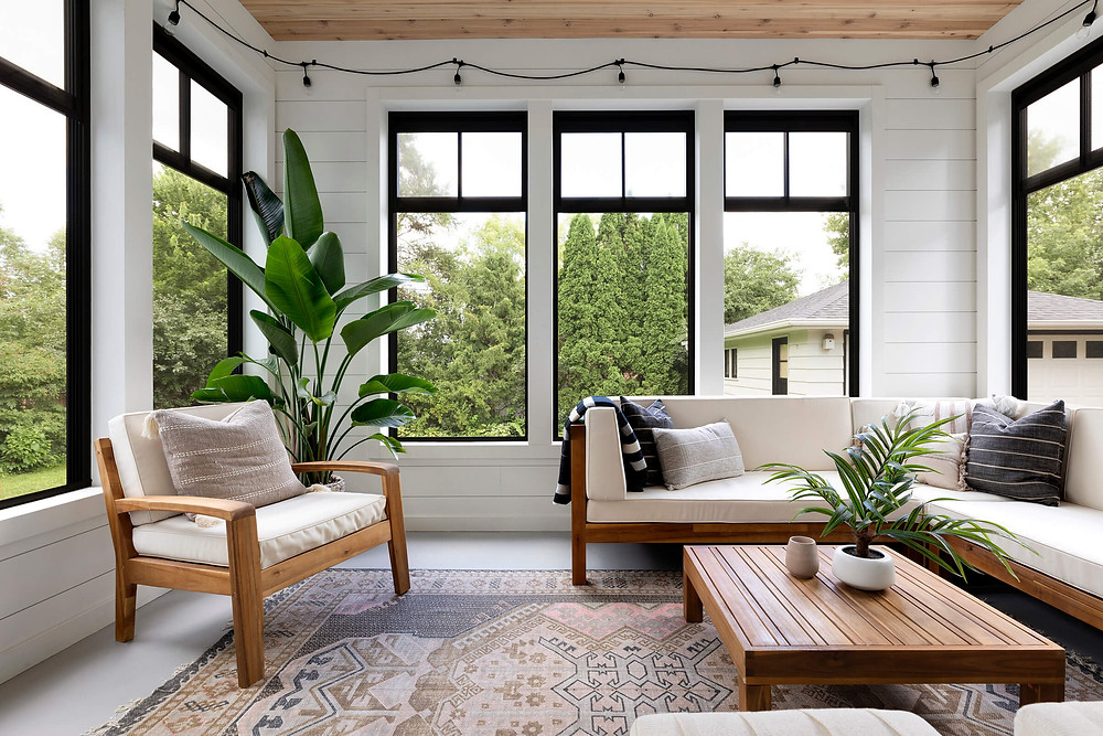 Comfortable four season porch with large black Marvin windows and reclaimed wood ceiling