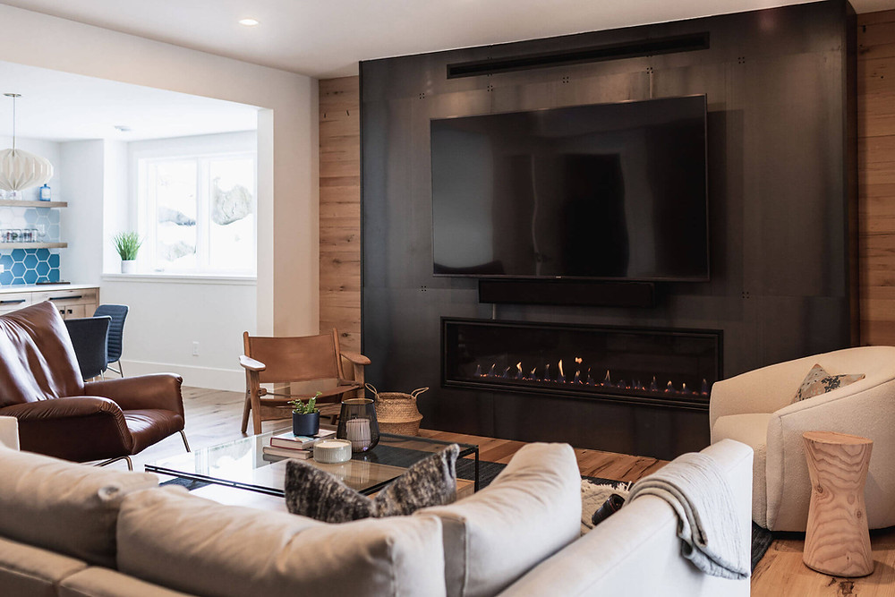 Large black metal fireplace surround with linear gas fireplace insert in cozy lower level living room with reclaimed wood accents