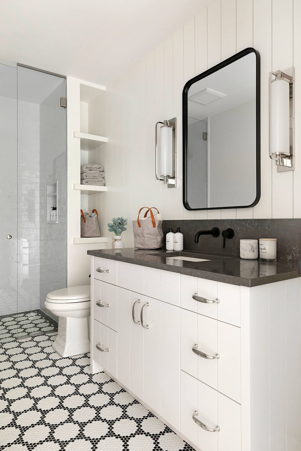 Black and white glass floor tile, painted v groove bathroom vanity, black countertop and polished nickel finishes.