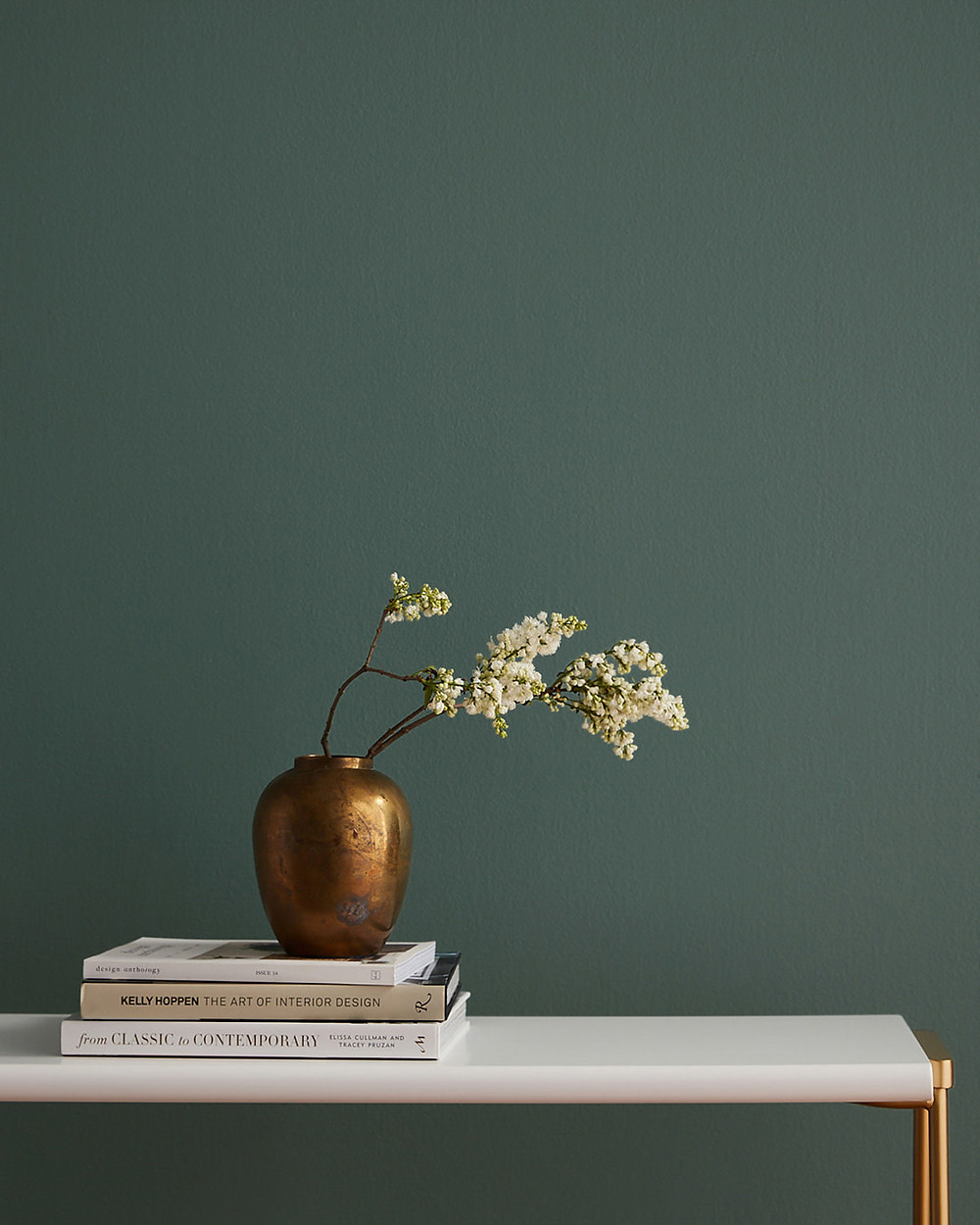 Current Moody moody green wall paint with brass planter and floral arrangement