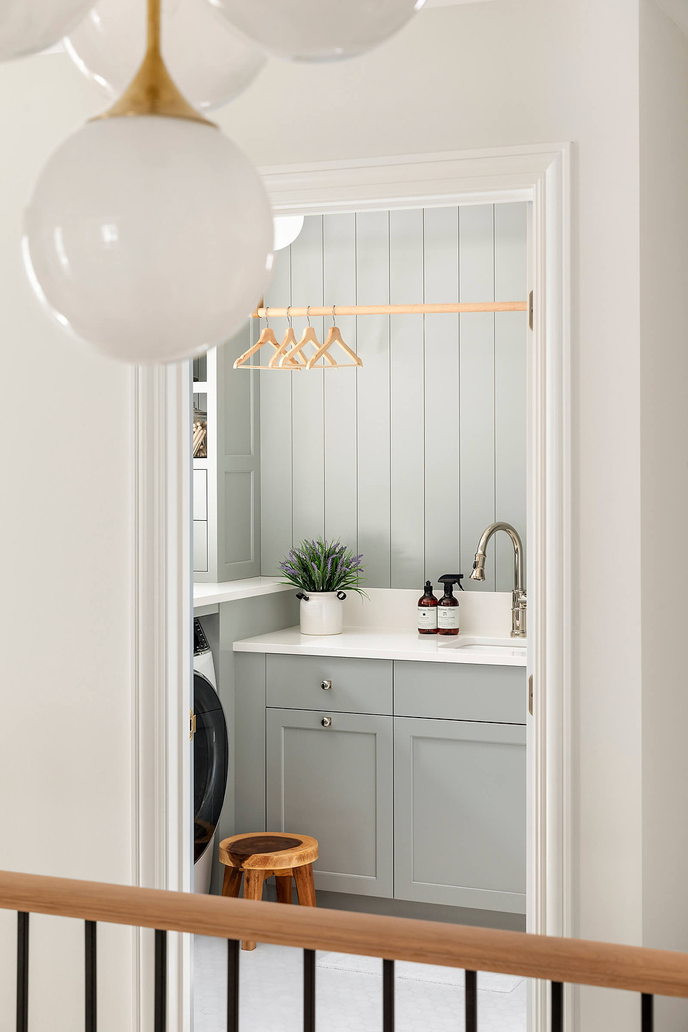 Laundry room makeover and why we chose an all monochromatic design with white marble hex tiles, polished nickel finishes and customized storage.