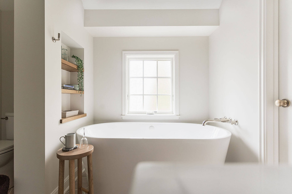 Primary owners suite bathroom freestanding bathtub with polished nickel wall mount tub filler and custom niche with floating oak shelves styled with bathroom decor