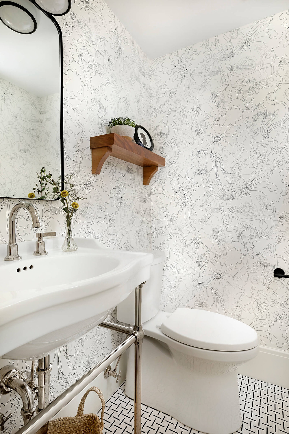 Powder bathroom with polished nickel console sink with playful sea creature wallpaper and black and white marble mosaic floor tile and walnut floating shelf