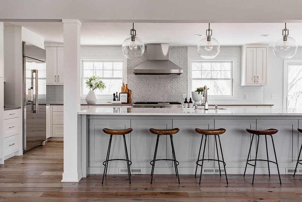 Open concept kitchen with large island with soft gray custom cabinetry and large range hood
