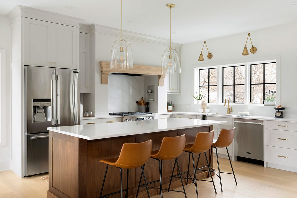 Bright farmhouse inspired kitchen with grey beige cabinetry, walnut island and brass finishes