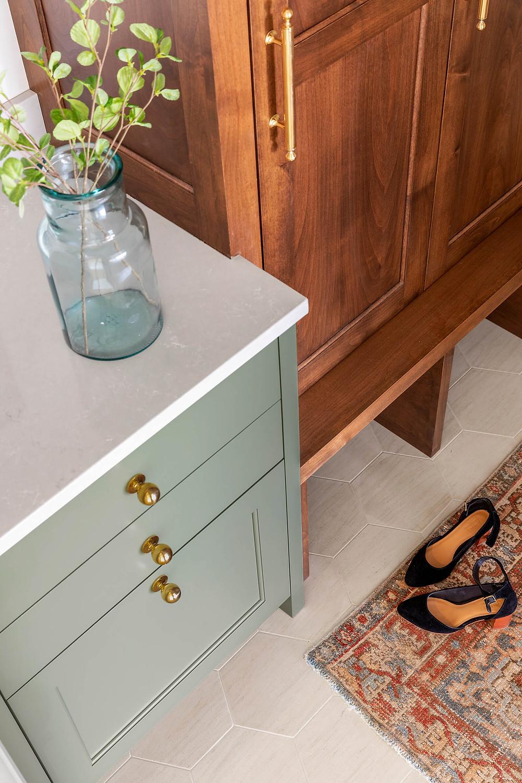 Traditional mudroom decor, vintage rug, alder stained mudroom cabinets, limestone hexagon floor tile with reeded glass pocket door.