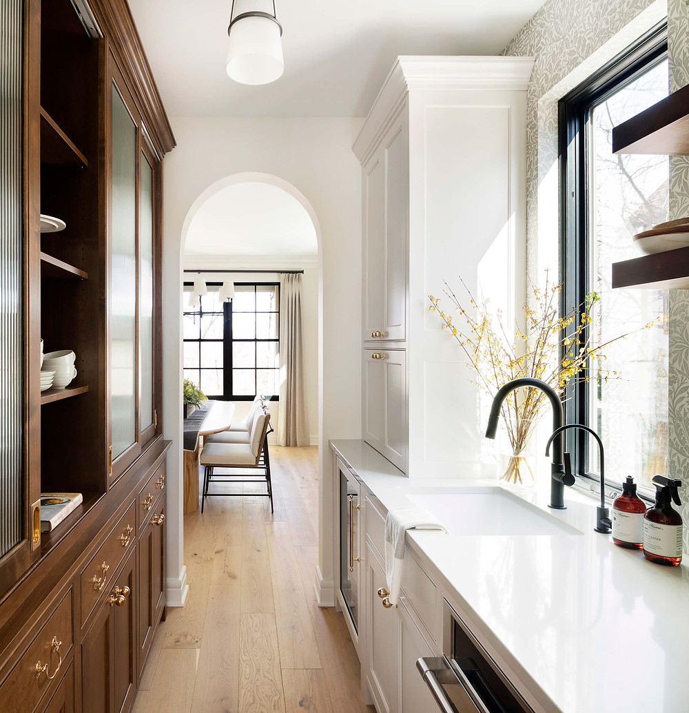 Charming butler's pantry with custom hutch-looking cabinetry, wallpaper and beautiful archways that connect kitchen to formal dining room