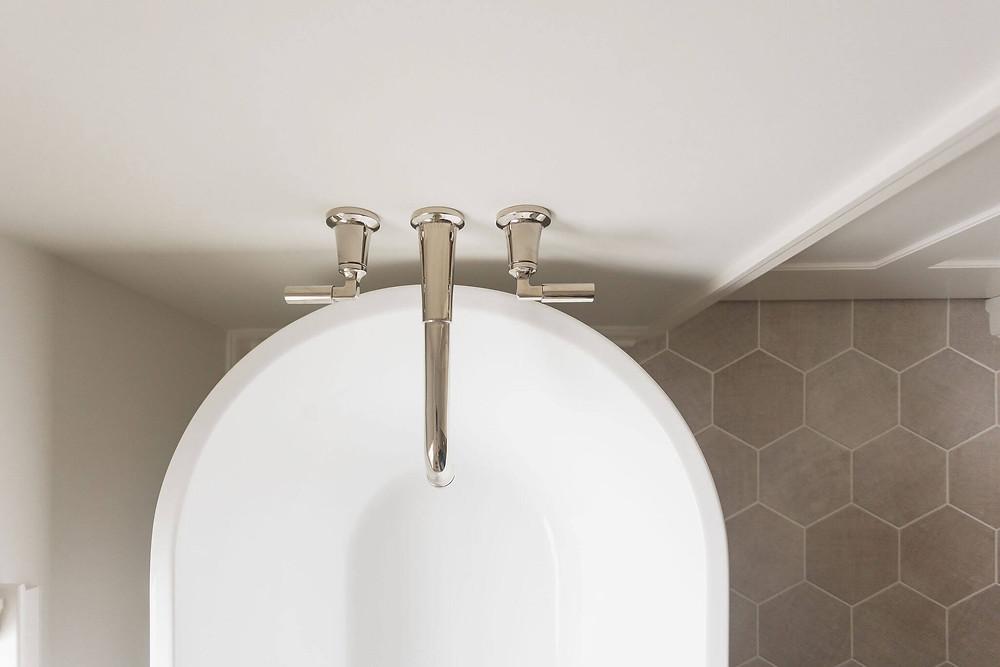 Primary suite bathroom wall mount tub filler in polished nickel over freestanding bathtub