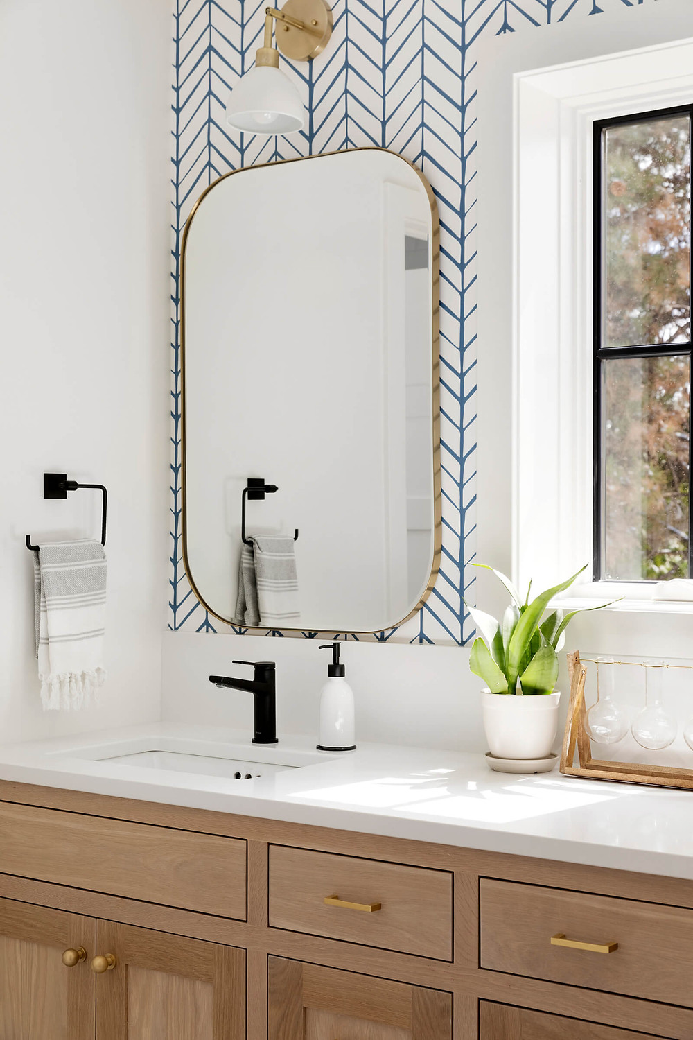white oak vanity, brass mirror, chevron wallpaper, blue wallpaper, black faucet, gold hardware, rectangle mirror, vanity mirror, vanity sconce