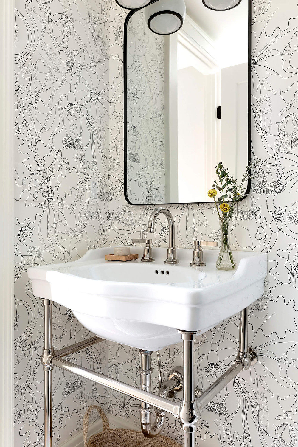 Powder bathroom with polished nickel console sink with playful sea creature wallpaper and black and white marble mosaic floor tile