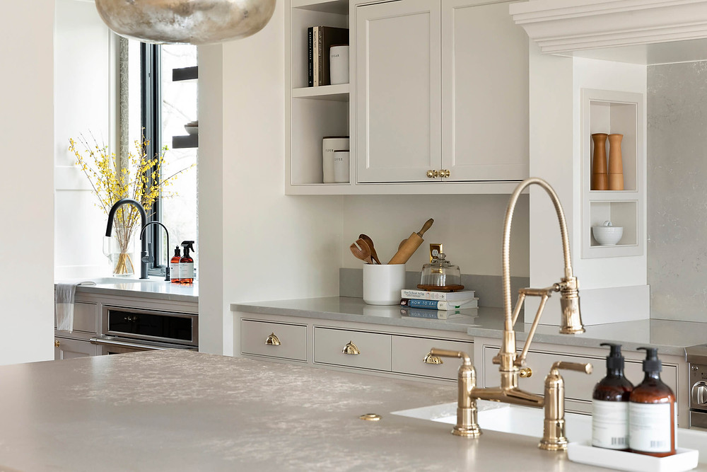 Small details in the kitchen with beautiful brass bridge faucet, open shelves and niche in range mantel