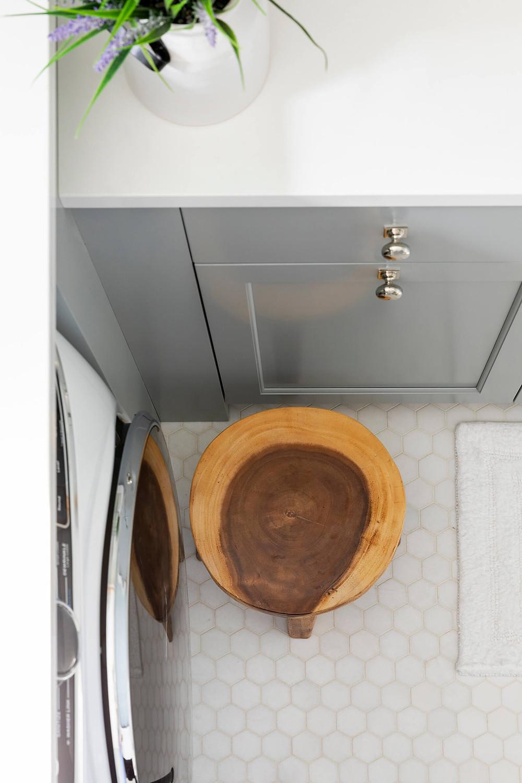 "Thassos 2"" hexagon floor tile in laundry room, blue cabinetry, white quartz countertop."