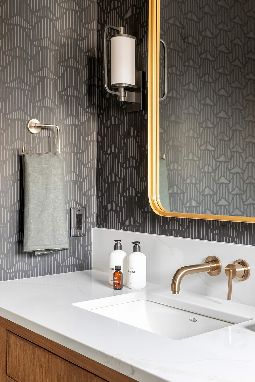 Black geometric Hygge & West wallpaper in kids bath room with beautiful brass wall mount faucet and mirror
