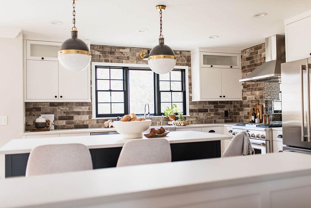 Mixed metal island pendants merge together black and white custom cabinetry with slab style doors, brick porcelain tile backsplash