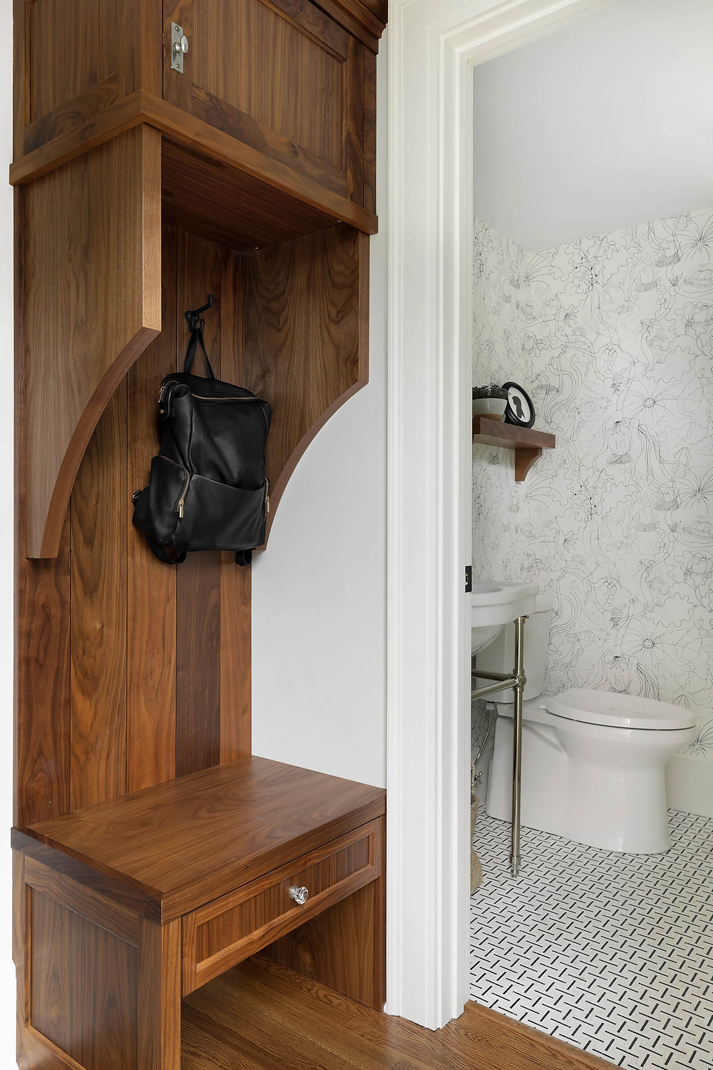 Walnut mudroom cabinet with vintage hardware seeing in to powder bathroom with playful wallpaper and black and white marble mosaic floor tile