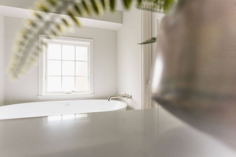 Primary owner's suite bathroom freestanding soaking bathtub with wall mount polished nickel tub filler and large privacy window