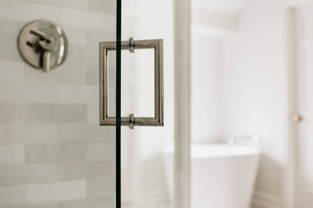 Primary bathroom suite shower with polished nickel finishes and white artisan subway tile