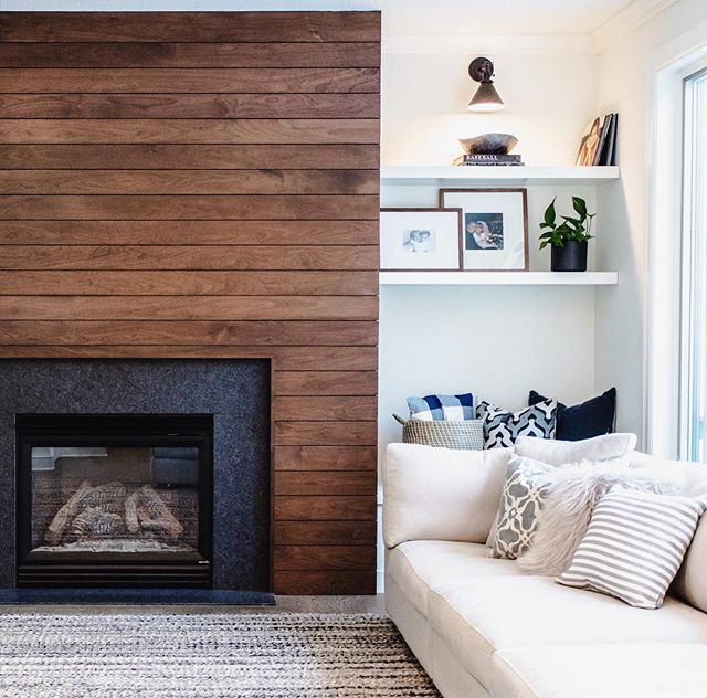 Walnut slat fireplace wall with cozy furniture and built-in shelves and bench