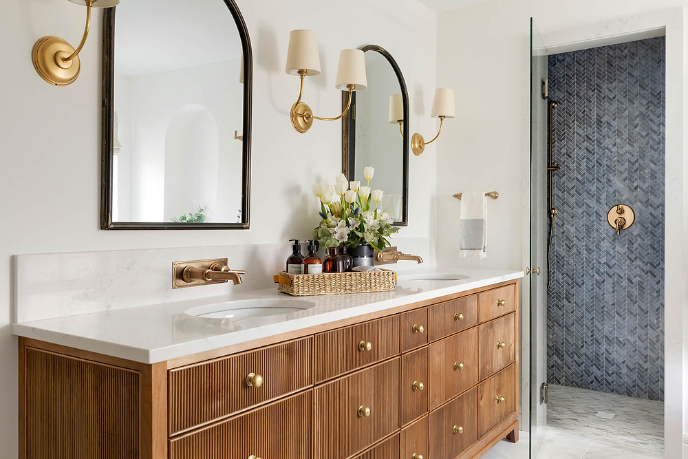 Custom alder reeded double vanity with beautiful brass wall mount faucets and arched mirrors