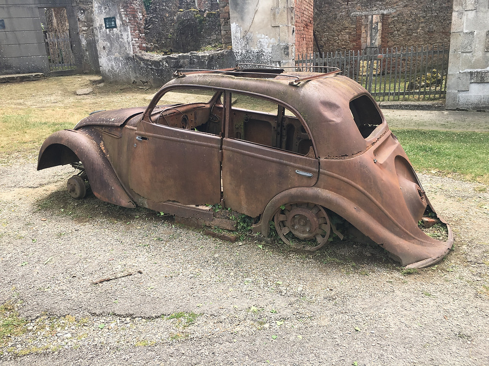A car that remains in place at the ruins of Oradour-sur-Glane