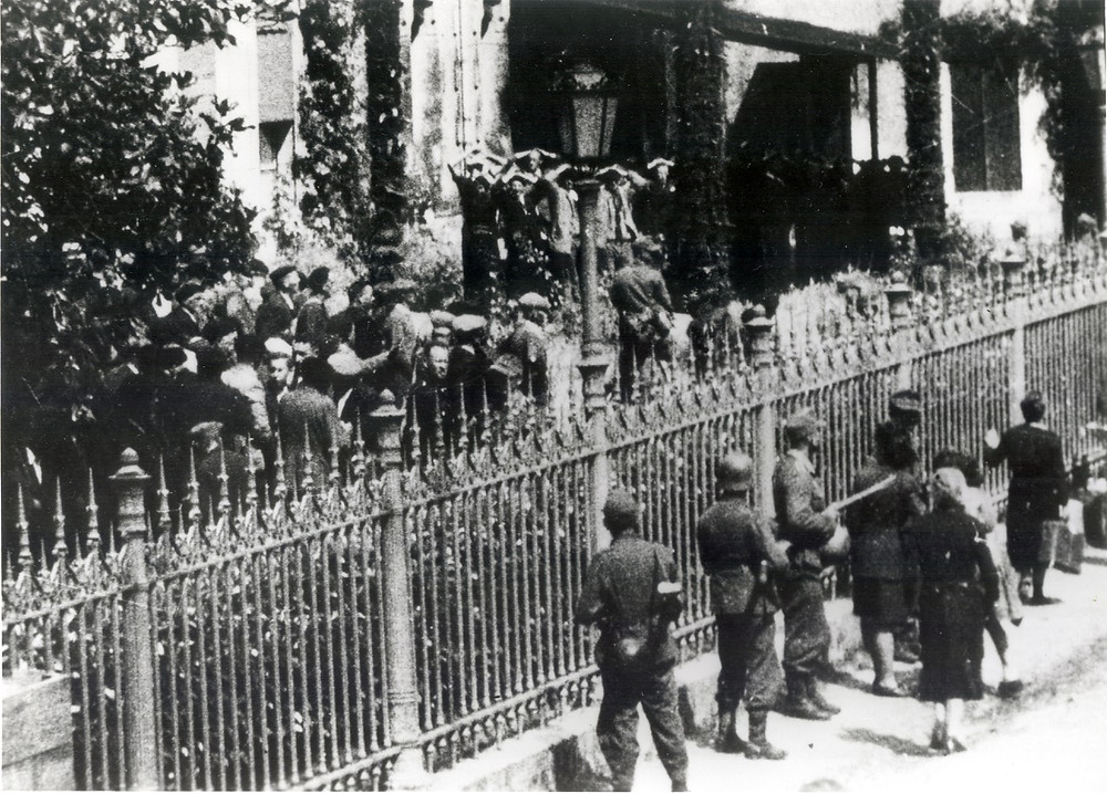 Hostages gathered in front of the mairie in Mussidan on 11 June 1944. Those on the left would be released. Those on the right with their hands in the air would be shot that evening. (Collection Patrice Rolli)