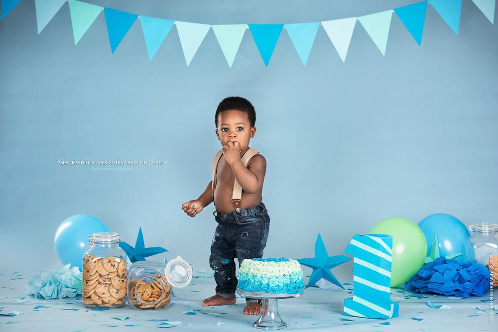 Enfant noir vêtu d'une salopette debout devant gâteau d'anniversaire les doigts dans la bouche
