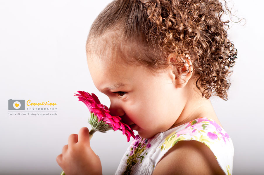 Photography child girl smells flower