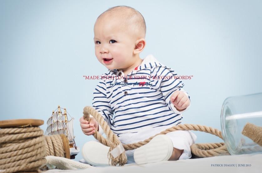 Bébé blanc en tenue de marin à rayures noires et blanches, légèrement de profil, souriant assis corde en main sur fond bleu avec une décoration marine